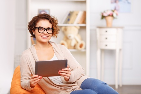arm chair: Pleasant positive content girl sitting in the arm chair and holding laptop while resting at home
