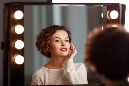 espejo: Cerca de la hermosa chica agradable encantados sentado delante del espejo y mirando directamente mientras se siente contenido