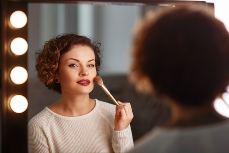 appealing: Close up of appealing young pleasant woman holding brush and making make up while sitting in front of mirror