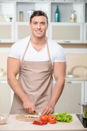 tough guy: Young smiling tough guy stands at the counter table and chops fresh vegetables. Stock Photo