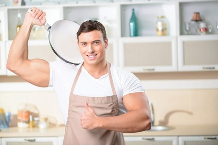 upholding: Appealing young strong man upholding a frying pan and showing thumbs up. Stock Photo