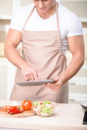strongly: Attractive young strongly built cook is busy with his tablet while standing beside the counter table.