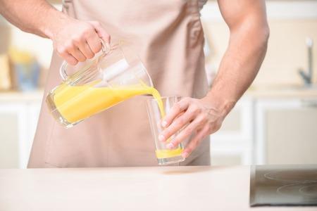 tomando jugo: Hombre de aspecto rudo joven en el proceso de verter el jugo de naranja en un vaso.