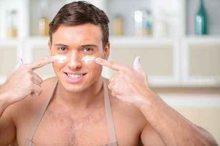 buoyant: Buoyant young muscular man enjoys himself in the kitchen by putting flour marks on his face.