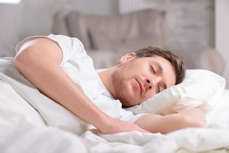 bed sheets: Good-looking young guy sleeps innocently in his bed before working day officially begins. Stock Photo