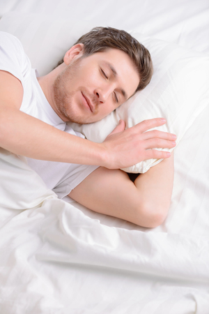 catnap: Attractive young single man doses off in his bed in the morning.
