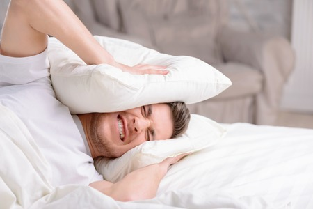 irritating: Handsome young man feels stressed when hides his head in pillows when irritating and loud alarm clock goes off.