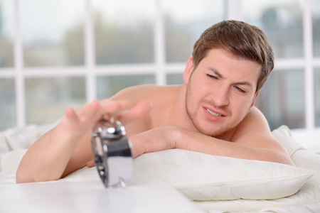 frowns: Stop the alarm. Handsome young man frowns irritated and reaches out to turn the alarm clock off. Stock Photo