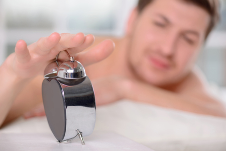 appealing: Appealing young man sleepily turns off the alarm clock.