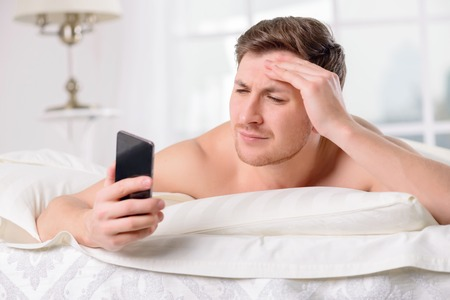 appealing: Appealing young man checks up his mobile social applications on smartphone while resting in bed.