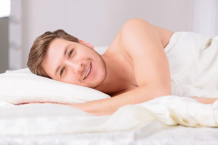 no rush: Young appealing man feels relaxed and unrushed while lying in bed on the side.