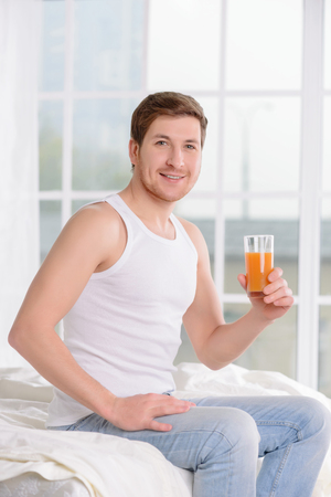 no rush: Handsome young man sits on the edge of his bad and holds a glass of fruit juice. Stock Photo
