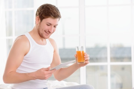 buena postura: Hombre joven guapo se sienta en la cama y mira su día-planificador, mientras que beber jugo de fruta fresca.