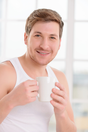 no rush: Attractive young man upholds freshly made cup of coffee.