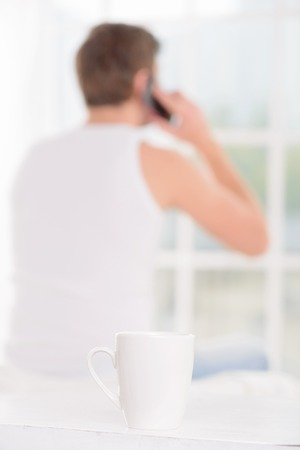 important phone call: Important call. Appealing young guy leaves his cup and walks over towards window while talking on the phone. Stock Photo