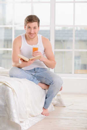 no rush: Day planning. Smiling good-looking guy sits on bed and checks his day-planner while drinking a glass of juice.