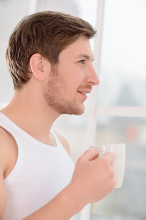 no rush: Young attractive man looks pensive while drinking his morning cup of coffee.