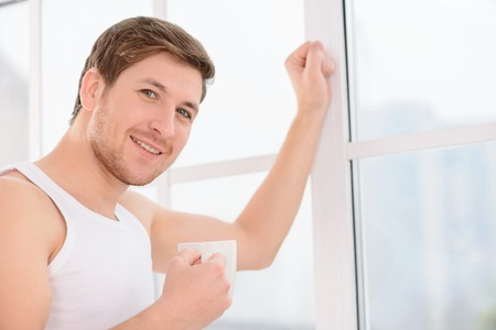 no rush: Young smiling man stands beside the window and enjoys his cup of coffee.