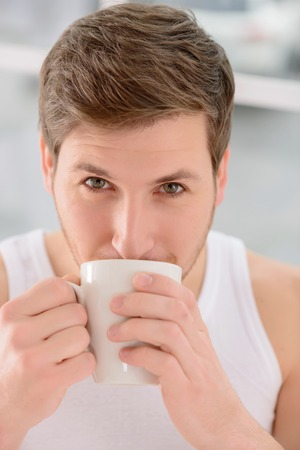 appealing: Appealing young guy is carefully sipping his morning hot cup of coffee.