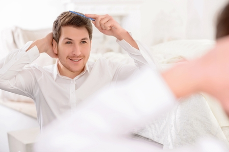 men standing: Appealing young guy smiles gently while combing his hair in front of the mirror. Stock Photo
