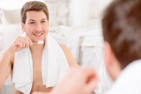 appealing: Young appealing smiling man is checking his reflection before brushing teeth.