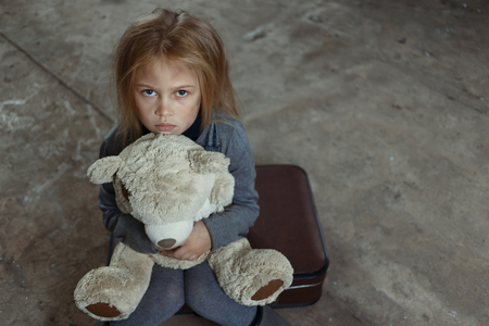 Top view of little sad depressed girl holding her toy and begging for help while feeling unhappy