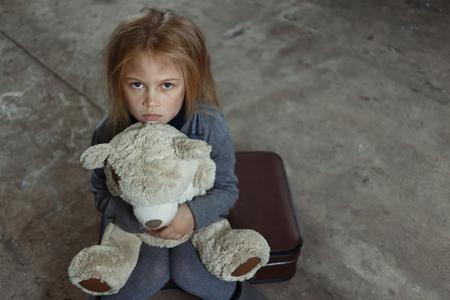 niños pobres: Vista superior de la niña triste deprimido sosteniendo su juguete y pidiendo ayuda mientras se siente infeliz Foto de archivo