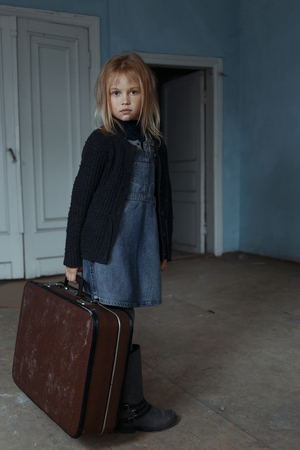 Poor sad depressed little girl holding suitcase and feeling gloomy while going to leave the room