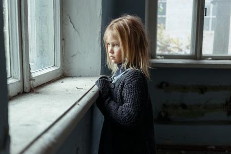 depresión: Cierre de depresión pobre niña que se coloca cerca de una ventana y mira a un lado mientras se siente desgraciada