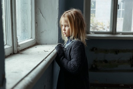 Close up of depressed poor little girl standing near window and looking aside while feeling miserable