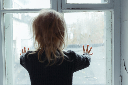 poor: Close up of hopeless little girl standing near window and holding her hands on the glass while waiting for parents Stock Photo