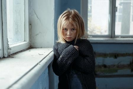 Gedoemde arme depressief meisje vouwen haar handen en staan haar raam terwijl verdrietig