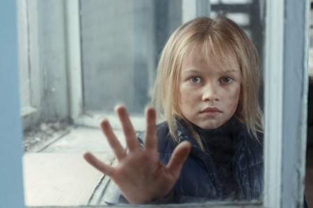 miserable: Little poor miserable girl standing near window and begging for help while holding her hand on glass