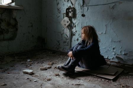 in tears: Pobre niña deprimida doblando las piernas y se sienta en el suelo mientras mira hacia arriba Foto de archivo