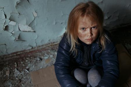 grief: Top view of depressed sad little girl sitting on the floor and looking up while feeling unhappy Stock Photo