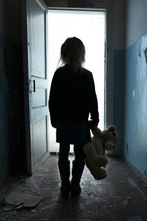 niños pobres: Pobre niña triste infeliz sosteniendo su juguete y de pie se volvió, dejando la habitación Foto de archivo