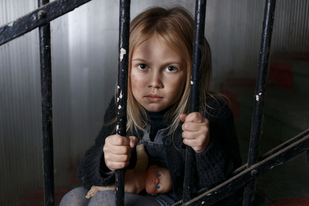 niños tristes: Pobre chica desesperada triste que se sienta en las escaleras y la celebración de barandilla mientras se siente deprimida Foto de archivo