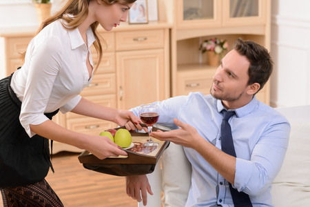 sexually: Sexually attractive pleasant housemaid holding tray and standing near man while flirting with him