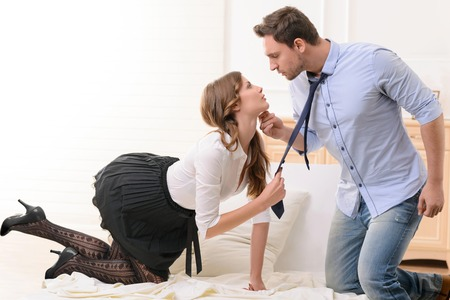 Sexually attractive beautiful housemaid holding tie of handsome man and looking at him while flirting on the bed