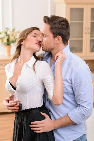 housemaid: Waist up of pleasant delighted defiant housemaid kissing with handsome man and feeling content