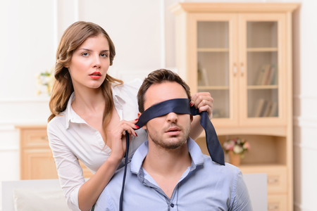 closing eyes: Pleasant attractive young housemaid holding tie and closing eyes of handsome man with it while flirting with him
