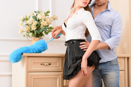 Seductive sexually attractive female housekeeper standing near chest of drawers with handsome man and kissing