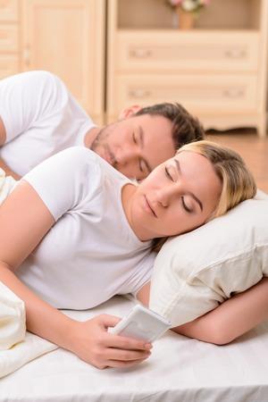 pareja en la cama: Agradable atractiva mujer que sostiene el teléfono móvil y la escritura de mensajes a su amante mientras está acostado en la cama con su marido Foto de archivo