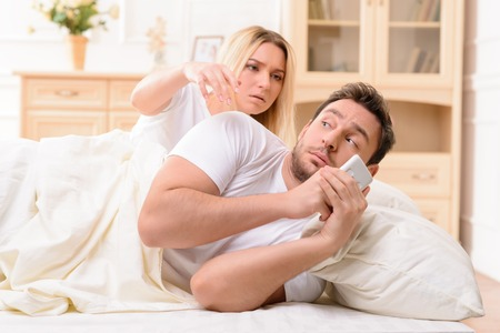 cocain: Shocked cheerless wife picking her husbands mobile phone and suspecting him in adultery while lying in bed