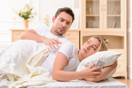 cheerless: Cheerless mad husband picking the mobile phone of his wife while suspecting him in adultery while lying in bed together.