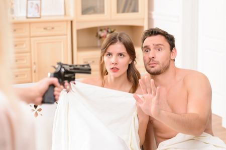 man with gun: Close up of gun in hands of ferocious wife holding gun and keeping it in front of her husband and the lover lying in bed Stock Photo