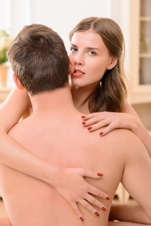 intrigue: Sexually attractive seductive woman biting ear of handsome man while embracing him Stock Photo