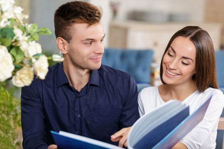 agreeable: Agreeable happy young couple sitting in the cafe and having a date while choosing food in the menu