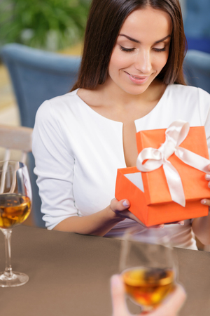 appealing: Top view of nice appealing woman holding box and opening it while sitting at the table
