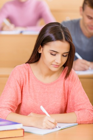 undergraduate: Appealing young female undergraduate looks focused while filling in her textbook.